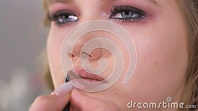 Opmaak toepassen De lippen van het model worden geschilderd met een make-up borstel Teller gloss toepassen Het werk van een make- stock video