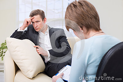 Depressed man talking with psychologist