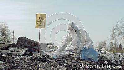 Oprócz planety oprócz planety od grata, Hazmat badacz w ochronnego mundur zbiera odmówić w torbie na śmiecie dla badać zbiory wideo