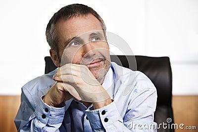 Optimistic businessman contemplating in office.