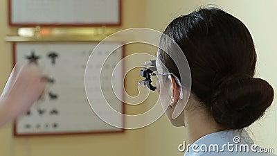 Optometrist doctor examining eyesight of patient stock video footage