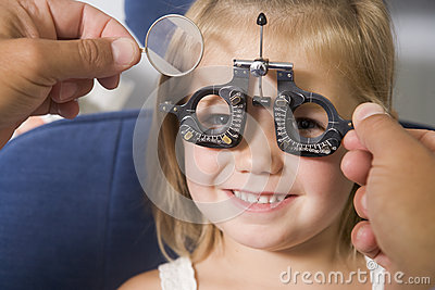 Optometrist in exam room with young girl