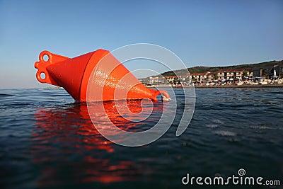 Orange anchor buoy floats on the sea.