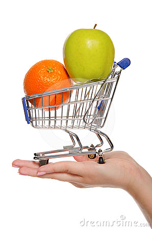 Orange and apple in shopping trolley on the palm