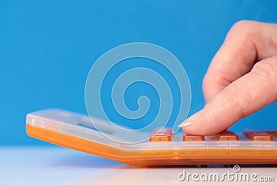 Orange Calculator with Fingers Closeup on Blue