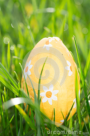 Orange easter egg nestled in the grass