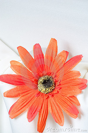 Orange fabric daisy on white linen