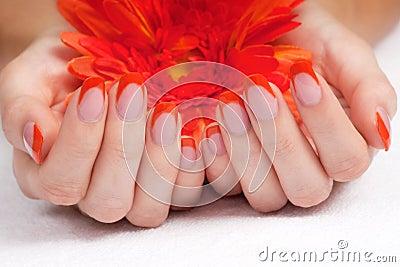 Orange fingernails and bright flower
