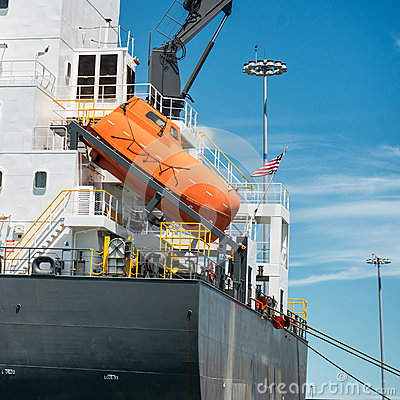 Free Orange Free-fall Life Boat For Emergency Crew Evacuation Installed On Cargo Ship Stock Photos - 60128383
