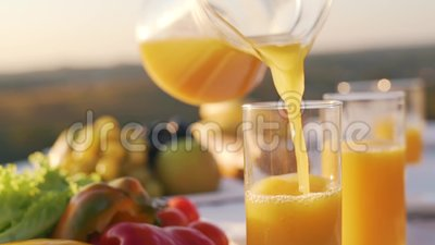 Orange fruktsaft hälls in i ett exponeringsglas stock video