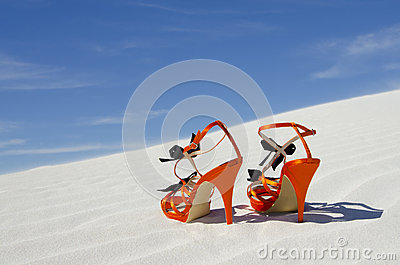 Orange high heels standing alone on sand dune