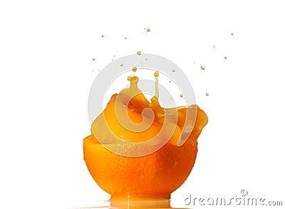 Orange juice splash inside an half orange isolated