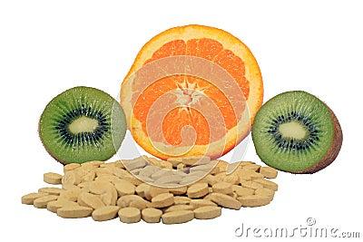 Orange and kiwi with vitamin pills