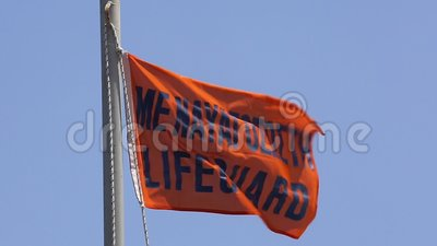 Orange Lifeguard Flag on a Beach in Greece Blowing in the Wind on a Summer Day stock video footage