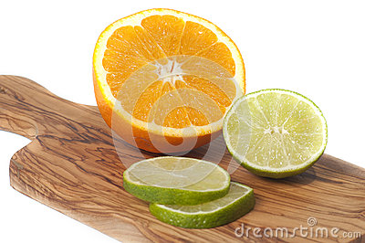 Orange and lime slices cut on a wooden board, isolated en white