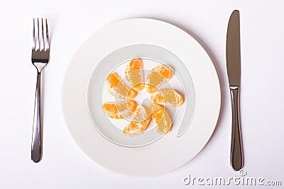 Orange mandarin on white plate
