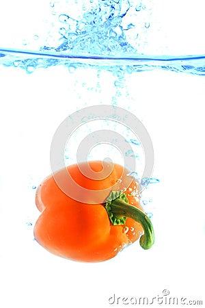 Orange pepper falling in water