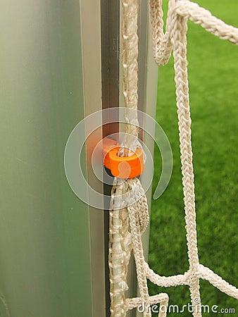 Orange plastic hanger in aluminum pole in soccer gate, soccer football net. Light green grass on football playground