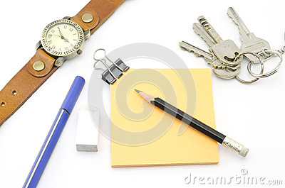 Orange post it with keys watch and bulldog clip and black pencil