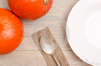 Orange pumpkins and plate with spoon