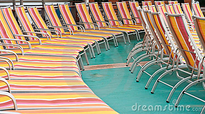 Orange and Red Chaise Lounges on Green Deck