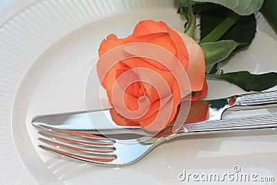Orange rose on cutlery