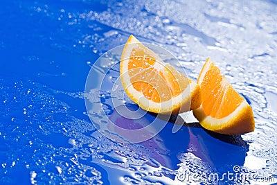 Orange slices on wet blue surface