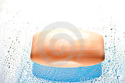 Orange soap bar on light abstract background.