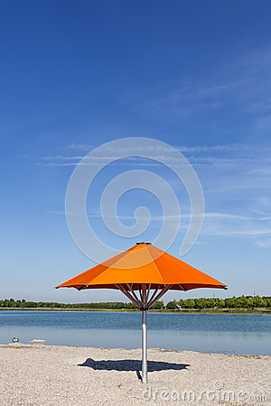 Orange sun umbrella on a bathing lake