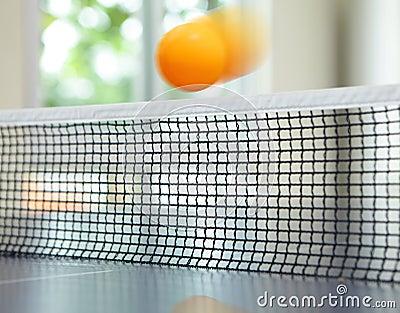 Orange table tennis ball moving over net