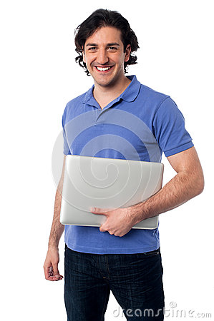 Ordenador portátil que se sostiene masculino joven hermoso
