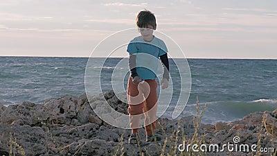 Orfano in vestiti sporchi sulla riva pietrosa piccolo ragazzo del rifugiato che gioca in fuga del mare migrazione e stile di vita stock footage