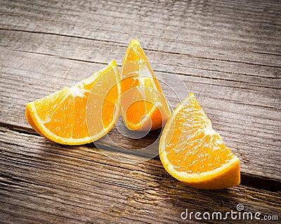 Organic orange fruit. Slices on wooden background