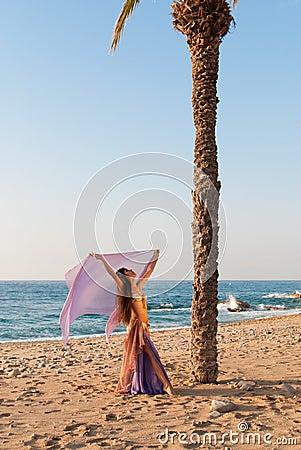 Oriental dancer performing on a beach