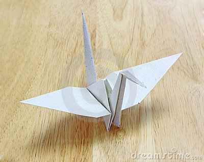 Origami Bird made of recycle paper on wood floor