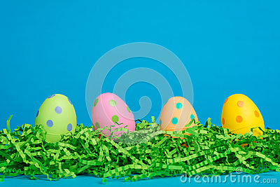 4 assorted decorated Easter eggs on a sky blue bac