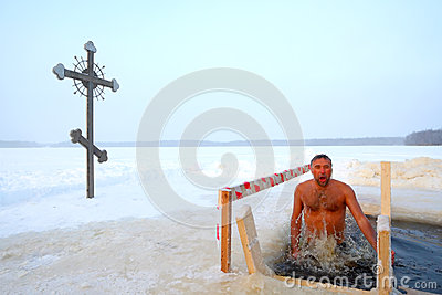 Orthodox believer takes a dip in ice cold water Editorial Stock Image
