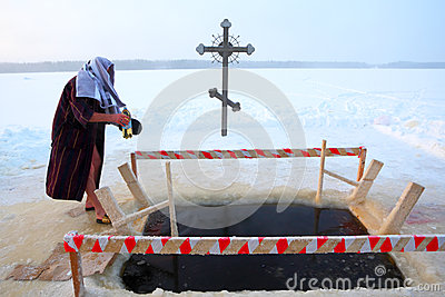Orthodox believer takes a dip in ice cold water Editorial Photo