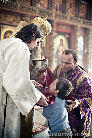 Orthodox bishop gives communion to a little boy Editorial Stock Photo