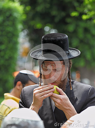 An orthodox Jew in long sidelocks picks citrus Editorial Stock Photo