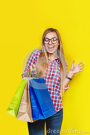 Free Ortrait Of Young Pretty Surprised Woman Holding Shopping Bags , Isolated On Yellow Background Stock Photos - 115247763