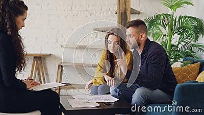 Os compradores novos adoráveis da casa dos pares estão olhando papéis e estão falando com corretor de imóveis então que sorriem e vídeos de arquivo