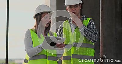 Os coordenadores ou os arquitetos t?m uma discuss?o no canteiro de obras que olha com o plano da constru??o jour do contre video estoque