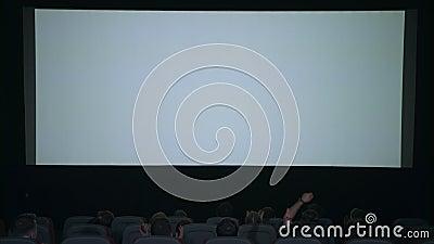 Os espectadores aplaudem em antecipação à sessão do filme na frente da tela branca vídeos de arquivo