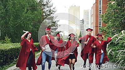 Os estudantes de graduação entusiasmado que correm ao longo da estrada no terreno que guarda os diplomas que vestem a graduação v video estoque
