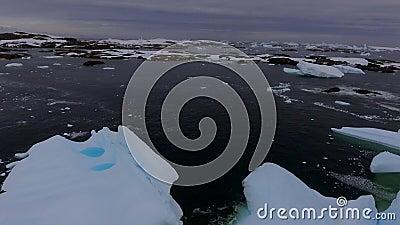 Os fragmentos do iceberg flutuam na água no crepúsculo Andreev vídeos de arquivo
