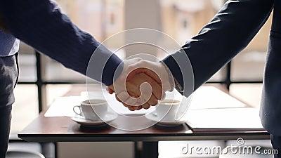 Os homens de negócio novos estão agitando as mãos, dizem olá!, estando na tabela no restaurante, povos de colaboração encontram-s filme