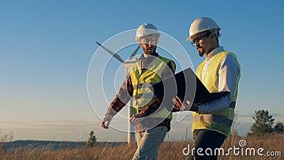 Os homens discutem um projeto ao verificar turbinas eólicas no campo Conceito ambiental da energia video estoque