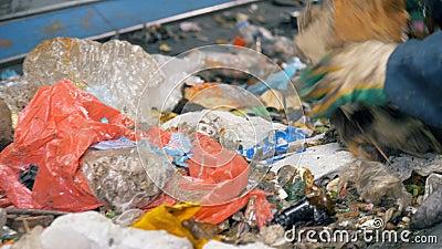 Os lotes do lixo vão em um transporte, ao ser classificado por um trabalhador especial 4K vídeos de arquivo
