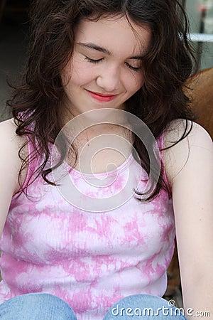 Os olhos de sorriso da menina adolescente fecharam-se
